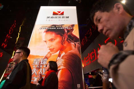 "people walk past a poster for the new ""Star Wars"" movie at a movie theater in Beijing on Jan. 9, 2016, as the record-breaking film opened in China. (Mark Schiefelbein/The Associated Press)"